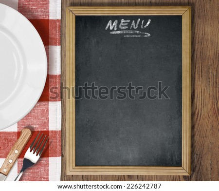 Menu chalkboard top view on table with dish, knife and fork - stock photo