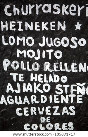 Menu painted on a brick wall from a local restaurant in Minca, Colombia 2014. - stock photo