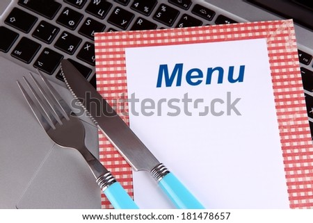 Menu with fork and knife on computer keyboard close up - stock photo