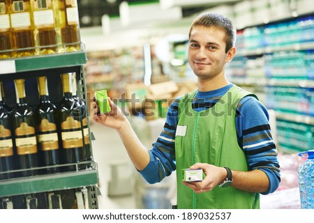 Merchandising. Sales assistant in supermarket lay out goods on supermarket shelves at store - stock photo
