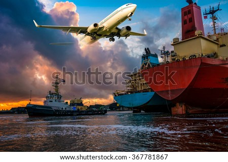 Merchant cargo ships assist by a tugboat are busy with mooring operations during sunset in port. Airplane is flying through the colorful clouds. Nice Industrial oil tanker/aviation background.  - stock photo