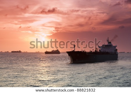 Merchant ships in silhouette backlit by the sun set - stock photo