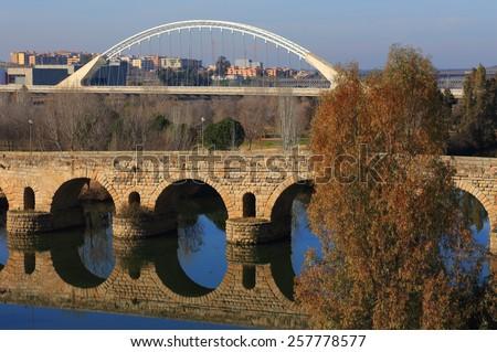Merida, Badajoz Province, Extremadura, Spain The Roman bridge reflecting on the Guadiana River. UNESCO World Heritage Site. The Modern Guadiana Bridge in background Eucalyptus trees in foreground. - stock photo