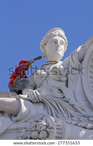 Merida, Yucatan  Mexico, January 2015: Man painting statue on a government building. - stock photo