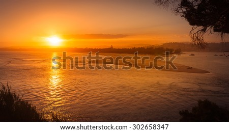 MERIMBULA, NSW, AUSTRALIA - DECEMBER 16, 2014: Warm orange sun going down over the sea bay in Merimbula,  the whale watching and tourist town in  New South Wales, Australia - aerial view - stock photo