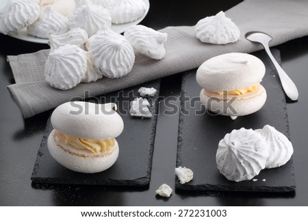 meringue cakes lie on a dark table - stock photo