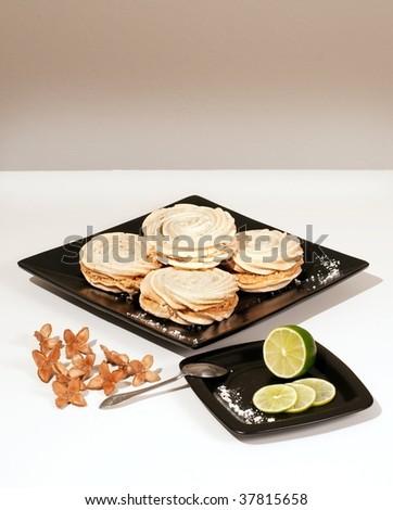 Meringue dessert on a black plate with lemon aside - stock photo