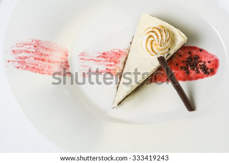 meringue on top of a cheesecake from above chocolate stick and raspberry coulis white plate   - stock photo