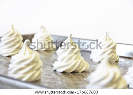 meringues on a baking sheet upclose - stock photo