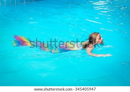 Mermaid girl swimming in the pool - stock photo
