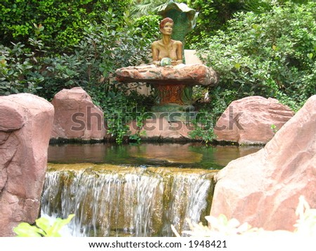 Mermaid Nesting Above Waterfall - stock photo