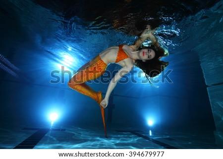 Mermaid posing underwater in the pool  - stock photo