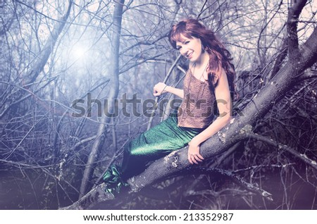 Mermaid sits in a tree - stock photo