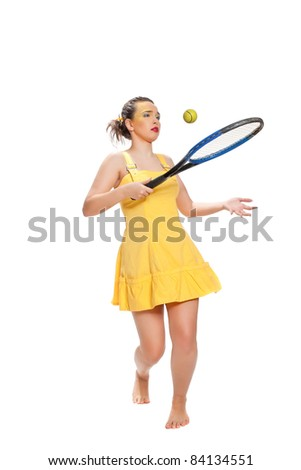 Merry beautiful girl in a yellow dress with a tennis racket posing on a white background - stock photo
