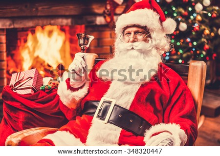 Merry Christmas and Happy New Year! Cheerful Santa Claus sitting at his chair and ringing a bell with fireplace and Christmas Tree in the background - stock photo