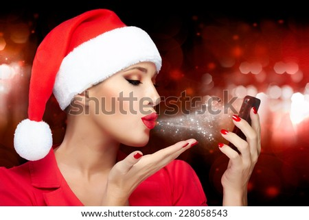 Merry Christmas. Beautiful Christmas girl in Santa hat makes a selfie sending kisses with a smart phone. Red lips and manicure. Happy people. Christmas greetings - stock photo