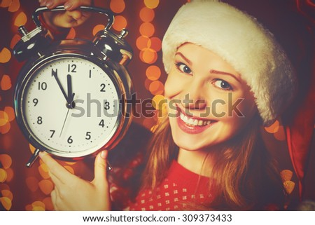 Merry Christmas! Cheerful woman in a Christmas hat with alarm clock - stock photo