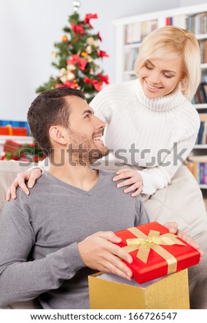 Merry Christmas! Handsome young man sitting on the couch and holding a gift box while her girlfriend standing behind him and smiling - stock photo
