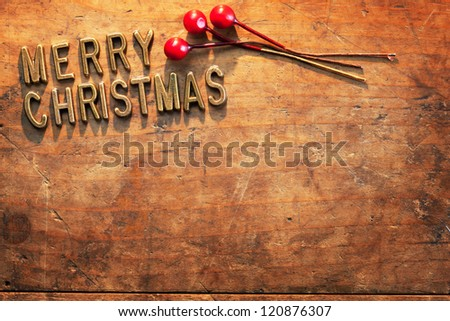 MERRY CHRISTMAS in brass lettering on a very old and worn wooden surface, Incandescent lighting. - stock photo
