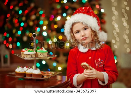 Merry Christmas - Little pretty girl in hat holding plate with cookies and candy for santa claus - stock photo