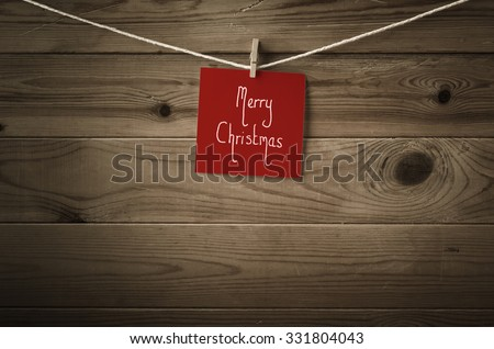 Merry Christmas message on a square of festive red note paper, pegged to a string washing line.  Wood plank background.  Low saturation and vignette gives a retro or vintage feel. - stock photo
