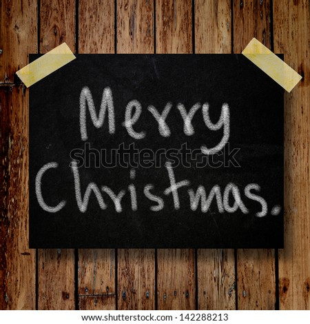 Merry Christmas on message note with wooden background - stock photo