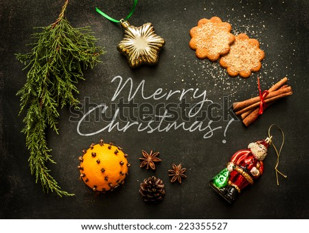 Merry Christmas - poster or postcard design. Vintage decorations, ginger cookies and spices on black chalkboard from above. - stock photo