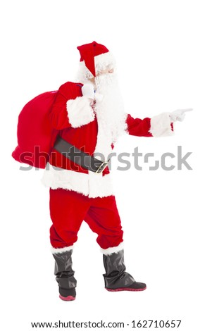 merry Christmas Santa Claus holding gift bag and pointing - stock photo