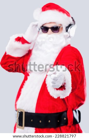 Merry Christmas to you! Cool Santa Claus in sunglasses adjusting his headphones and pointing you while standing against grey background - stock photo