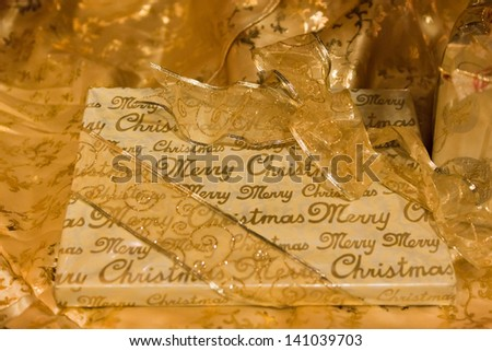 Merry Christmas wishing paper wraps a present along with a golden ribbon set on a background of golden cloth. - stock photo