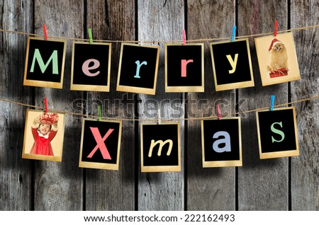 Merry christmas words hanging on clothesline on wood background. - stock photo