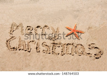 Merry Christmas written in the sand with star - stock photo
