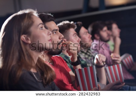 merry company in the cinema, young people watch movies, film, - stock photo