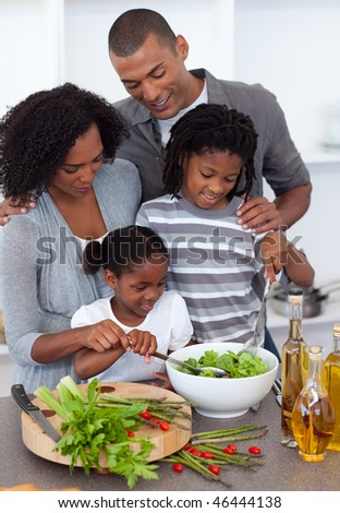 Merry family preparing dinner together in the kitchen - stock photo