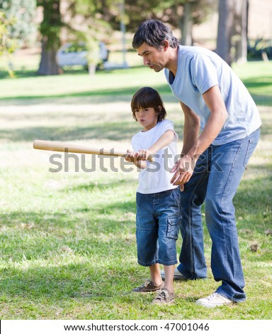 Merry father playing baseball with his son in the park - stock photo