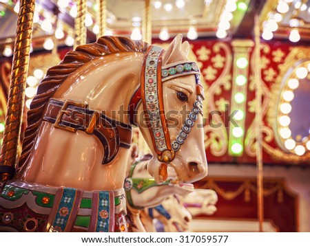 merry-go-round wooden horses toned with a retro vintage instagram filter app or action effect (SHALLOW DOF) - stock photo