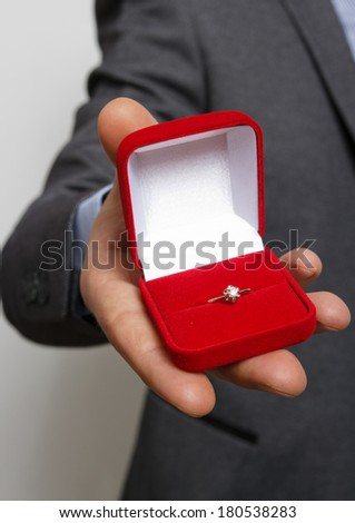 Merry proposal. male hand holds out the engagement ring in red box to the camera - stock photo
