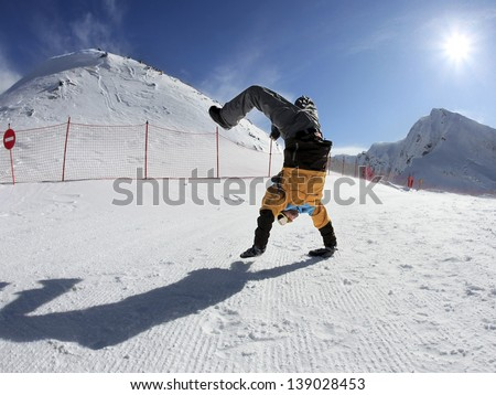 Merry Snowboarder standing on hands in mountains against the blue sky and sun - stock photo