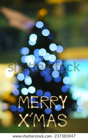 Merry X' Mas sparkle firework writing with defocused light Christmas tree - stock photo