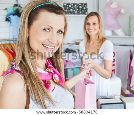 Merry young woman getting shopping bags from the saleswoman in a clothes store - stock photo