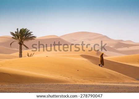 MERZOUGA, MOROCCO, APRIL 13, 2015: Local man walks on Dunes Erg Chebbi near Merzouga - stock photo