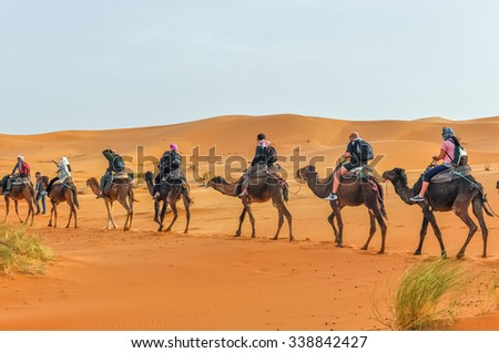MERZOUGA, MOROCCO, APRIL 13, 2015: Tourists take part in camels trip on sand dunes of Erg Chebbi - stock photo