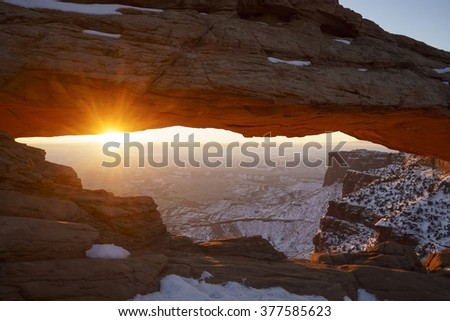 Mesa Arch sunrise in Canyonlands National Park near Moab, Utah, USA.  This rare wintertime scenic with snow and red rocks is a tourist attraction of the southwestern deserts and Colorado Plateau. - stock photo
