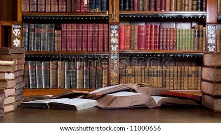 Mess in studying room. Many vintage books in desk. - stock photo