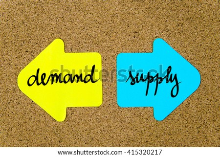 Message Demand versus Supply on yellow and blue paper notes as opposite arrows pinned on cork board with thumbtacks. Choice conceptual image - stock photo