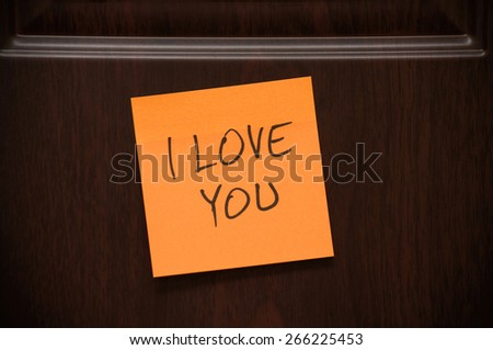 """Message """"I Love You"""" handwritten on the sticky note on the wooden door - stock photo"""