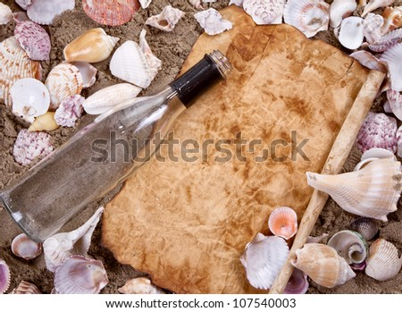 Message in a bottle on a sandy beach copy space on aged paper surrounded by seashells - stock photo