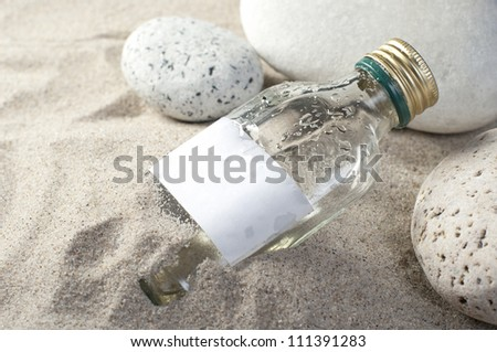 Message in a bottle on sand beach background. - stock photo