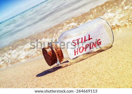 """Message in a bottle """"Still hoping"""" on sandy beach. Creative business and faith concept.  - stock photo"""