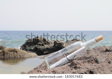 Message in Bottle on the Rocks near Beach - stock photo